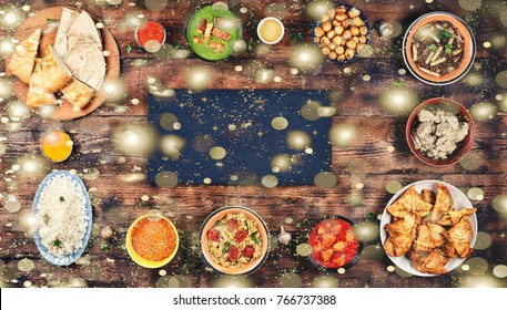 Concept: Christmas, New Year. Falling snow, golden snowflakes. Assorted indian food on a wooden background. Dishes and appetizers of indian cuisine. Bowls and plates with indian food