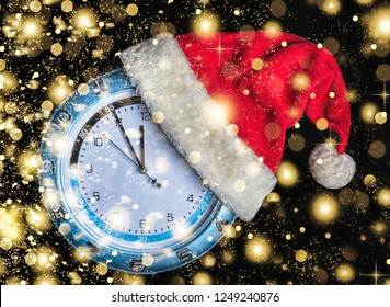 Concept: Christmas and New Year. Santa's hat is worn on a wall clock and the arrows show the approaching New Year's midnight on black background, golden falling snow