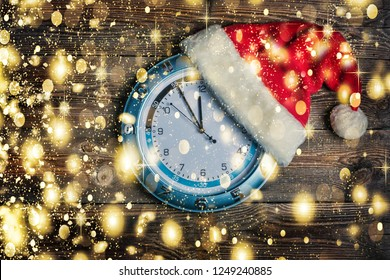 Concept: Christmas and New Year. Santa's hat is worn on  wall clock and arrows show approaching New Year's midnight.  on wooden background with copy space and golden falling snow
