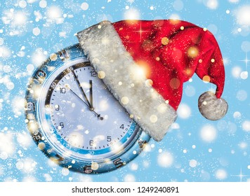 Concept: Christmas and New Year. Santa's hat is worn on wall clock and arrows show  approaching New Year's midnight on blue background, golden falling snow