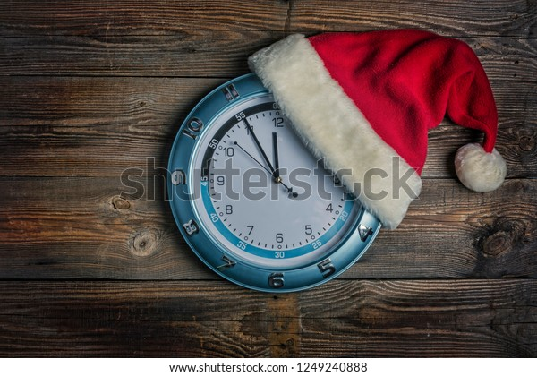 Concept: Christmas and New Year. Santa's hat is worn on wall clock and arrows show  approaching New Year's midnight  on  wooden background with copy space