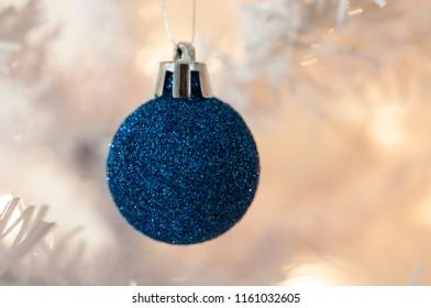 Concept of Christmas Postcard. Blue sparkling ball on the Christmas tree, selective focus