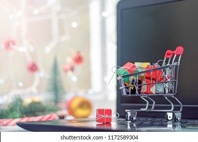 Concept of Christmas shopping online.Shopping cart with gifts stands on a laptop on the background of a festive decor.