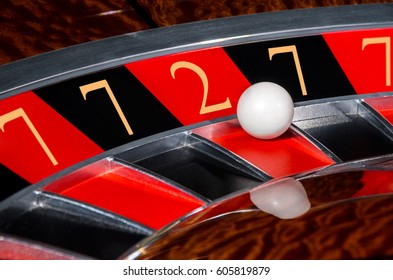 Concept of classic casino code 7-7-2-7-7 lucky numbers roulette wheel with black and red sectors and white ball