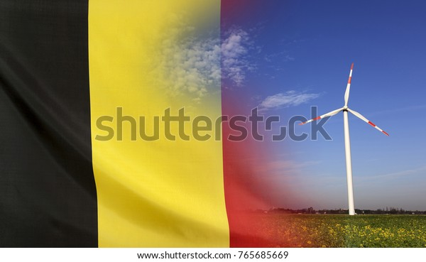 Concept clean energy with flag of Belgium merged with wind turbine in a blue sunny sky and green grass with flowers