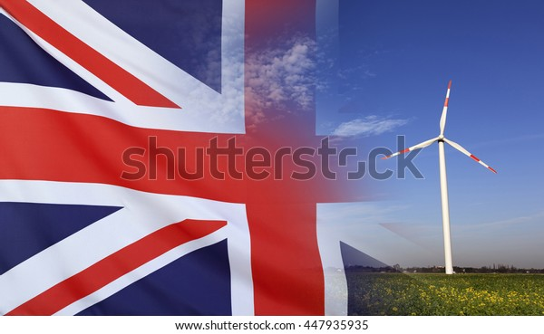 Concept clean energy with flag of Great Britain merged with wind turbine in a blue sunny sky and green grass with flowers