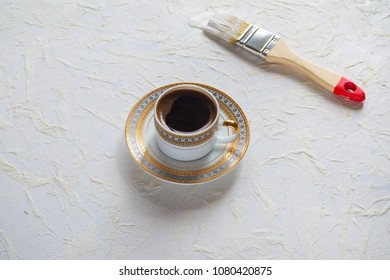 The concept of the coffee break in the workplace. A Cup of black coffee and a paintbrush on a painted white wall.