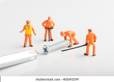The concept of a collective solution to any problem. Miniature toy workers join a real screw with a screwdriver. Close-up view.
