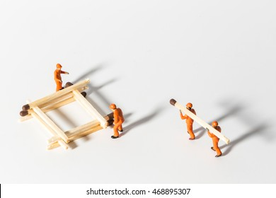 The concept of a collective solution to any problem. Miniature toy workers build a house from matches. Workers perform disposal of the Chief. Close-up view.