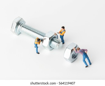 The concept of a collective solution to any problem. Miniature toy workers tightening a nut of a new bolt on white background. Close-up view.