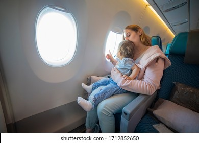 concept: comfortable flight with a child. young beautiful mother is sitting in an airplane chair holding on her lap a little cute toddler and points with  a finger in the porthole
