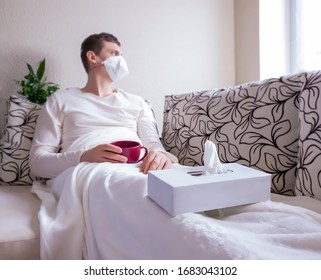 The concept of the common cold or seasonal flu. A young man in a mask looks out the window, lying on a sofa. Drinks a hot healing drink. Quarantine.