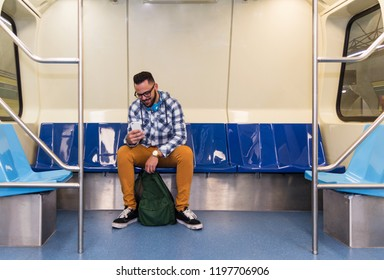 Concept of commute, urban life, aspirations, concentration, journey. Handsome commuter student man on smartphone using app texting sms message inside train compartment.