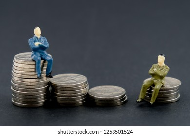 The concept of comparison of the rich and poor man. Toy man sitting on a stack of coins on a black background.