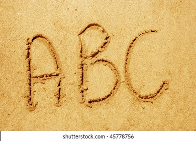 Concept or conceptual abstract set or collection of fonts in sand on exotic beach sea shore handwritten in a sandy texture background in summer for alphabet,education,letter,text,vacation or tourism