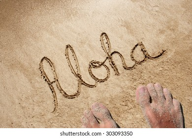 Concept, conceptual Aloha text handwritten in sand on a beach background with feet in an exotic island for tropical, summer, sea, ocean, calendar, travel, holiday, sunny, tourism, resort, time, relax