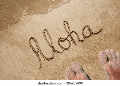 Concept or conceptual Aloha text handwritten in sand on a beach with feet in an exotic island for tropical, summer, sea, ocean, calendar, travel, holiday, sunny, tourism, resort, time or relaxet