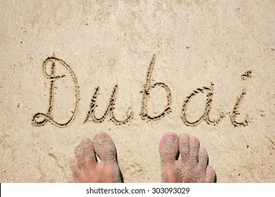 Concept or conceptual Dubai handwritten in sand on a beach with feet in an exotic island for tropical, summer, sea, ocean, calendar, travel, holiday, sunny, tourism, resort, time or relax
