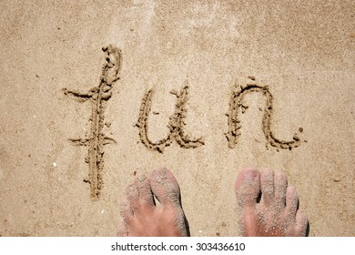 Concept or conceptual fun text handwritten in sand on a beach with feet in an exotic island for tropical, summer, sea, ocean, calendar, travel, holiday, sunny, tourism, resort, time or relax
