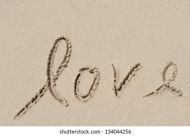 Concept or conceptual hand made or handwritten Valentine`s day text in sand on a beach in an exotic islandConcept or conceptual hand made or handwritten love text in sand on a beach in exotic island