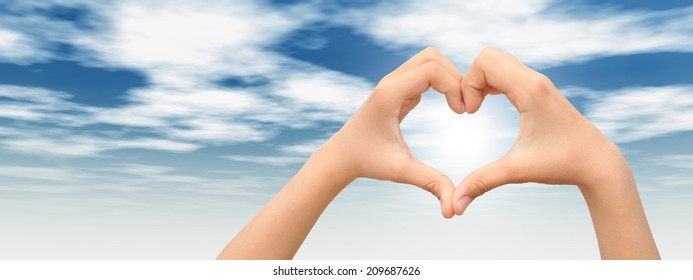 Concept or conceptual heart shape or symbol made of human or woman and man hand over a blue sky at sunset background, metaphor to love, valentine, romantic, couple, wedding, romance, summer or sunrise