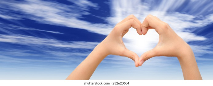 Concept or conceptual heart shape or symbol made of human or woman and man hand over a blue sky background, metaphor to love, valentine, romantic, couple, wedding, romance, summer or sunrise