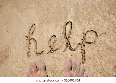 Concept or conceptual help text handwritten in sand on a beach in an exotic island background with feet  metaphor for sun, ecology, bio, eco, natural, life, world, global, protect or environmental