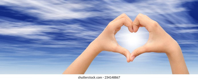 Concept or conceptual human male man and woman hands in love, Valentines shape or symbol heart over blue sky background, metaphor to romance, romantic, wedding, honeymoon, holiday, vacation or couple