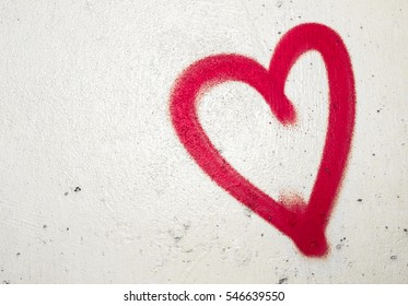 Concept or conceptual painted red abstract heart shape love symbol, dirty wall  background, metaphor to urban and romantic valentine, grungy style.