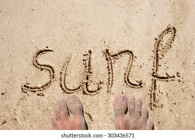 Concept or conceptual Surf text handwritten in sand on a beach with feet in an exotic island for tropical, summer, sea, ocean, calendar, travel, holiday, sunny, tourism, resort, time or relax