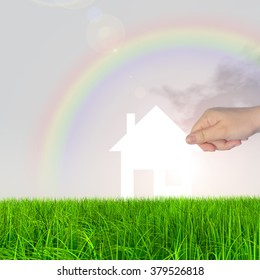 Concept conceptual white paper house held in hand by a man in a green summer grass over a rainbow sky background with clouds, a symbol for construction, eco, ecology, loan, mortgage, property or home