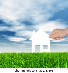 Concept or conceptual white paper house held in hand by a man in a green summer grass over a blue sky background with clouds, a symbol for construction, eco, ecology, loan, mortgage, property or home