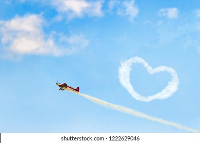 Concept of confession in love. Small red airplane draw a valentine in a blue sky.