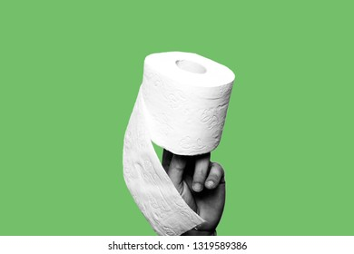 Concept of constipation, diarrhea, problem. Hand holding a toilet paper roll. The subject is black and white. The background is green. Isolated