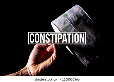 "Concept constipation. Hand holding a toilet paper roll in chiaroscuro with black background. In foreground a text saying ""Constipation"""