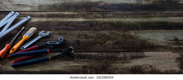 Concept of construction or DIY tooling on old wooden house renovation board with folding meter, screwdriver, wrench and spanner, banner