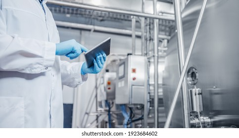 Concept control food industry banner. Factory worker inspecting production line tanker in of dairy with computer tablet.