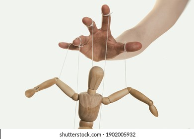 Concept of control. Marionette in human hand. Close-up.