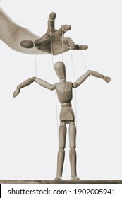 Concept of control. Marionette in human hand. Black and white.
