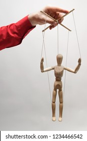 Concept of control. Marionette in woman's hand.