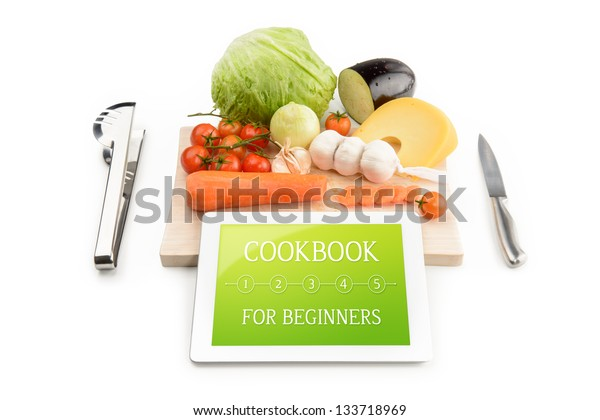 Concept of cookbook for beginners on the tablet computer. Near the tablet computer is a cutting board, cutlery and food. Isolated on white.