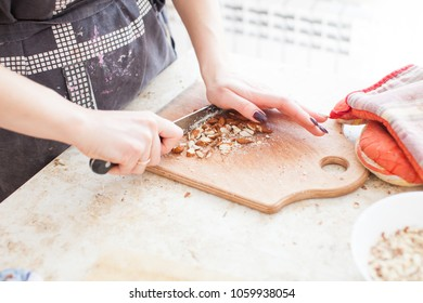The concept of cooking. The confectioner cuts the almonds for the cake.