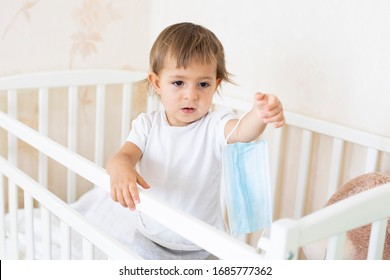 concept coronavirus covid-19  quarantine, security, hygiene. little cute baby is in the crib at home and is holding a medical mask