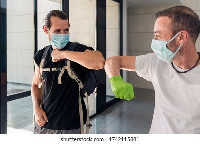Concept: Coronavirus, covid-19. Two male friends greeting each other with their elbows at the entrance of a building. New normality, pandemics and epidemics prevention.