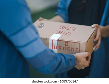 Concept for Coronavirus panic shortage of coronavirus tests to prevent the spread of the covid19. Caucasian man delivering cardboard of covid19 test kit with the mention urgent to a caucasian woman.
