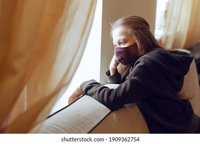 Concept of coronavirus quarantine. Child wearing protective face mask during flu virus, looking out of window. COVID-19 - self isolation. Teen girl forced to stay at home. Prevention epidemic.