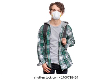 Concept of coronavirus quarantine. Student wearing medical protective mask to health from influenza virus, isolated on white background. Teen boy in face mask with backpack. COVID-19 - back to school.
