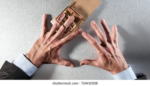 concept of corporate financial temptation with hurt businessman hands catching euro bank note, hurt by a mouse trap for investment trick, danger, bait or strategy question, above view