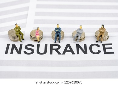 The concept of corporate health insurance from the employer. People figurines sit on piles of coins and on insurance contracts.