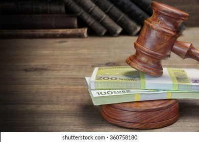 Concept For Corruption, Bankruptcy, Bail, Crime, Bribing, Fraud, Auction. Judges or Auctioneer Gavel, Soundboard, Bundle Of Euro Cash And Old Law Book  Library On The Rough Wooden Table Background.